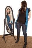 Mujer que mira a uno mismo en espejo Imagen de archivo libre de regalías