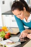 Mujer que mira verduras de la cocina de la receta de la lectura de la tablilla Imagen de archivo