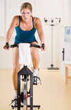 Mujer que monta la bicicleta inmóvil en club de salud Imagen de archivo libre de regalías