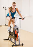 Mujer que monta la bicicleta inmóvil en club de salud Foto de archivo