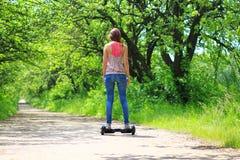 Mujer que monta un tablero eléctrico de la libración de la vespa al aire libre -, rueda de balanza elegante, vespa del girocompás Imagen de archivo