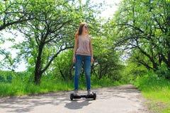 Mujer que monta un tablero eléctrico de la libración de la vespa al aire libre -, rueda de balanza elegante, vespa del girocompás imagenes de archivo