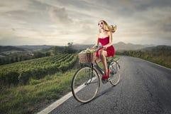 Mujer que monta una bici Fotografía de archivo