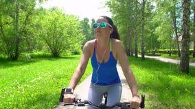 Mujer que monta una bici con un monitor del ritmo cardíaco del smartwatch Concepto elegante del reloj Vidrios que llevan felices  almacen de video
