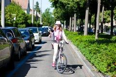 Mujer que monta una bici mientras que hace cuadros Imágenes de archivo libres de regalías