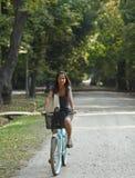 Mujer que monta una bicicleta Imagenes de archivo