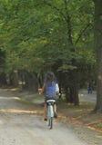 Mujer que monta una bicicleta Imagen de archivo libre de regalías