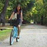 Mujer que monta una bicicleta Fotos de archivo