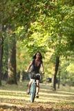Mujer que monta una bicicleta Fotos de archivo libres de regalías