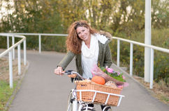 Mujer que monta una bicicleta Imágenes de archivo libres de regalías