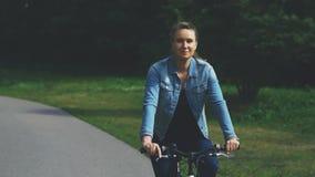 Mujer que monta una bicicleta en el parque metrajes