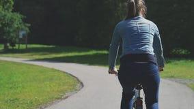 Mujer que monta una bicicleta en el parque almacen de metraje de vídeo
