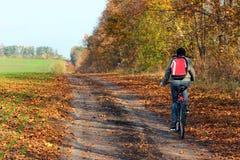 Mujer que monta una bicicleta en una carretera nacional Foto de archivo libre de regalías