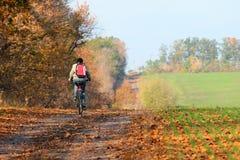 Mujer que monta una bicicleta en una carretera nacional Fotografía de archivo libre de regalías