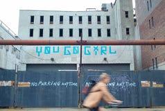 Mujer que monta una bicicleta por un estacionamiento con la señalización del arte de la calle Imagen de archivo libre de regalías