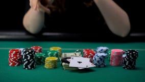 Mujer que muestra a aces pares y que toma todos los microprocesadores y dinero, ganador del casino del juego imagen de archivo libre de regalías