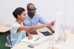 Mujer que muestra algo a su colega en el ordenador portátil Fotos de archivo libres de regalías