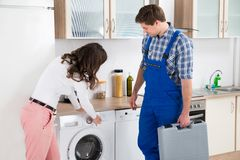 Mujer que muestra daño en lavadora al reparador imagen de archivo libre de regalías