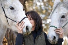 Mujer que muestra el afecto a sus caballos Fotos de archivo libres de regalías