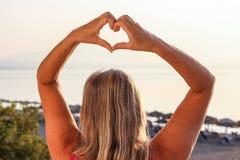 Mujer que muestra el corazón con sus fingeres y que hace frente al mar temprano adentro fotos de archivo