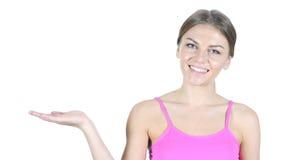 Mujer que muestra el producto a un lado, fondo blanco Fotos de archivo