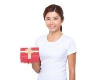 Mujer que muestra el rectángulo de regalo rojo hermoso foto de archivo