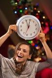 Mujer que muestra el reloj delante del árbol de navidad Imágenes de archivo libres de regalías