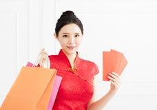 Mujer que muestra el sobre y los panieres rojos Fotos de archivo