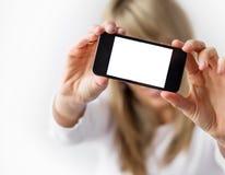 Mujer que muestra el teléfono móvil con la exhibición vacía Fotos de archivo libres de regalías