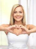 Mujer que muestra forma del corazón Imagenes de archivo