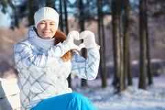 Mujer que muestra forma del corazón con las manoplas blancas en luz del sol en el invierno Foto de archivo