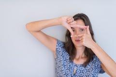Mujer que muestra gesto de mano que enmarca Imagenes de archivo