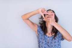 Mujer que muestra gesto de mano que enmarca Imagen de archivo
