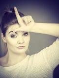 Mujer que muestra gesto del perdedor con L en la frente Foto de archivo libre de regalías