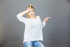 Mujer que muestra gesto del perdedor con L en la frente Fotografía de archivo libre de regalías
