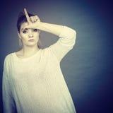 Mujer que muestra gesto del perdedor con L en la frente Fotografía de archivo