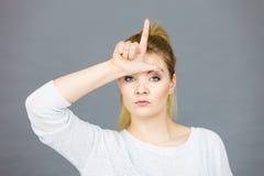 Mujer que muestra gesto del perdedor con L en la frente Imagen de archivo libre de regalías