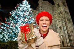 Mujer que muestra la caja de regalo cerca del árbol de navidad en Florencia, Italia Imágenes de archivo libres de regalías