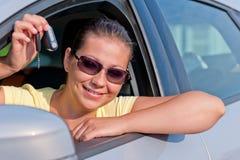 Mujer que muestra la llave de su nuevo coche Imagen de archivo libre de regalías