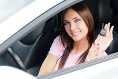Mujer que muestra la llave del coche Imagen de archivo libre de regalías