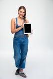 Mujer que muestra la pantalla de tableta en blanco Imagenes de archivo