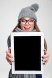 Mujer que muestra la pantalla de tableta en blanco Imagen de archivo libre de regalías