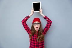 Mujer que muestra la pantalla de tableta en blanco Fotos de archivo libres de regalías