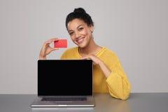 Mujer que muestra la pantalla del ordenador portátil y la tarjeta de crédito negras Fotografía de archivo libre de regalías