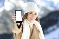 Mujer que muestra la pantalla elegante del teléfono en vacaciones de invierno Imagen de archivo