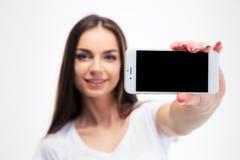 Mujer que muestra la pantalla en blanco del smartphone Imágenes de archivo libres de regalías