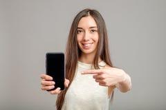 Mujer que muestra la pantalla en blanco del smartphone Imagen de archivo libre de regalías