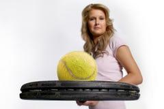 Mujer que muestra la pelota de tenis Foto de archivo libre de regalías