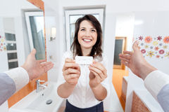 Mujer que muestra la prueba de embarazo positiva Fotos de archivo libres de regalías