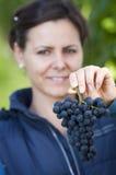 Mujer que muestra la uva roja Imágenes de archivo libres de regalías